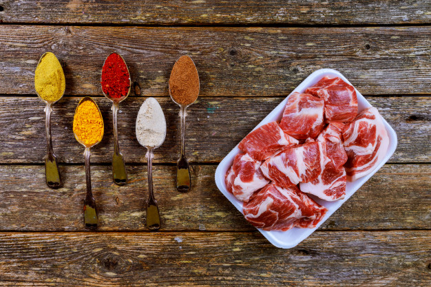 pork-raw-meat-ingredients-with-different-spices-old-wooden-table_73110-1565